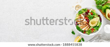 Grilled chicken meat and fresh vegetable salad of tomato, avocado, lettuce and spinach. Healthy and detox food concept. Ketogenic diet. Buddha bowl dish on white background, top view. Banner.