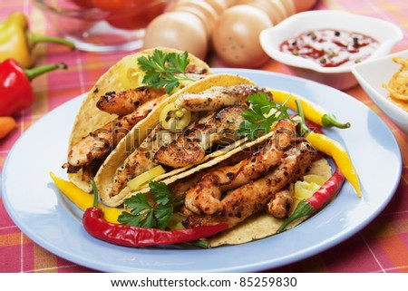 Grilled chicken meat and hot chili peppers in taco shells