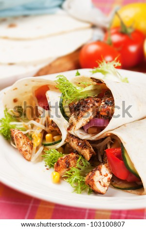 Grilled chicken meat and vegetable salad in tortilla wrap