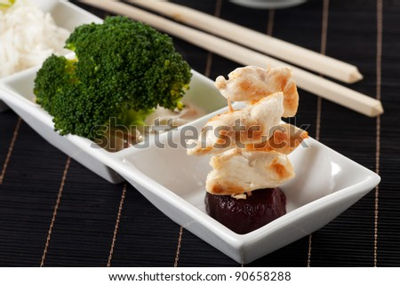grilled chicken meat on a skewer with chop sticks - stock photo
