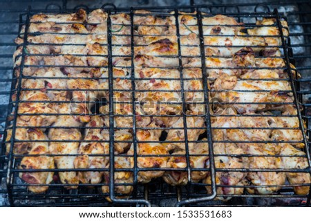 Grilled chicken meat on an iron grill barbecue grill closeup. #1533531683