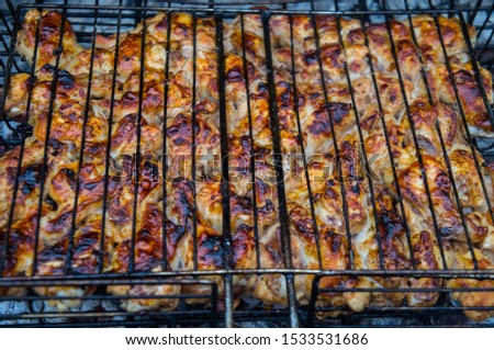 Grilled chicken meat on an iron grill barbecue grill closeup. #1533531686
