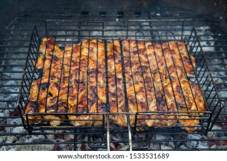 Grilled chicken meat on an iron grill barbecue grill closeup. #1533531689