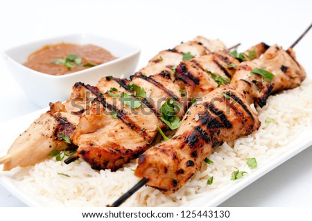 grilled chicken on bamboo skewers with a peanut dipping sauce