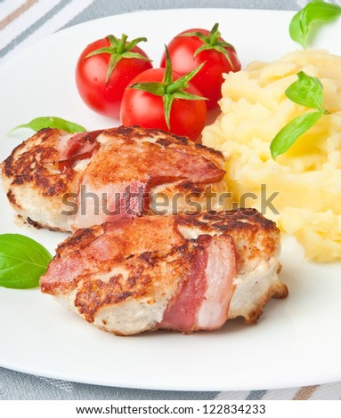 grilled chicken patties wrapped strips of bacon and mashed potatoes