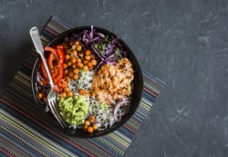 Grilled chicken, rice, spicy chickpeas, avocado mash, cabbage, pepper buddha bowl on dark background, top view. Delicious balanced food concept