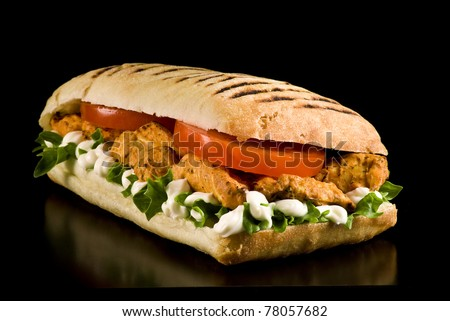 Grilled chicken sandwich on a black background