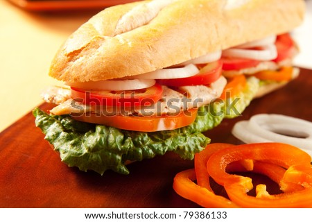Grilled chicken sandwich with orange peppers, tomato, lettuce and onions