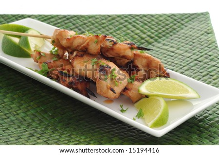 Grilled chicken satay served with lime wedges.