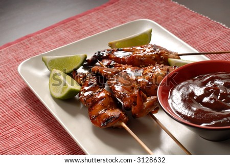 Grilled chicken satay, with juicy limes, sesame seeds and honey BBQ dipping sauce