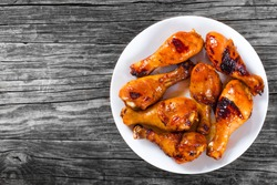 Grilled chicken sticky drumsticks marinated with honey and ginger on a white dish, top view