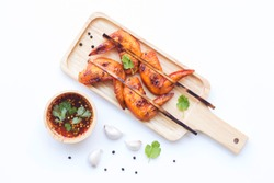 Grilled chicken wings in wooden dish with vegetable and spices flat lay on white background, food ideas concept