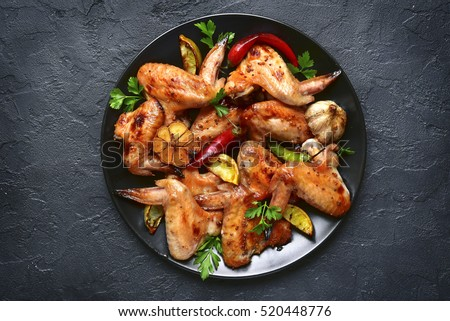 Shutterstock Grilled chicken wings on a black plate on a stone,concrete or slate background.Top view.
