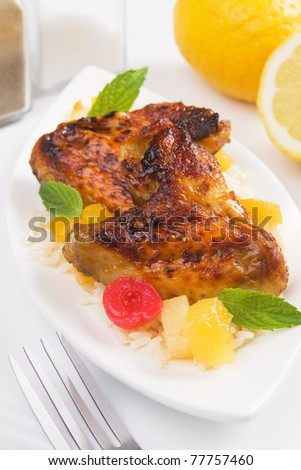 Grilled chicken wings served with rice and tropical fruit