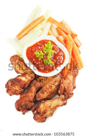 Grilled chicken wings with chili sauce and fresh vegetables
