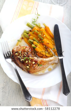 Grilled chicken with baby carrots on white plates