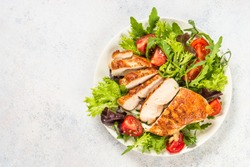 Grilled chicken with fresh salad. Keto diet, healthy eating. Top view on white table with space for text.
