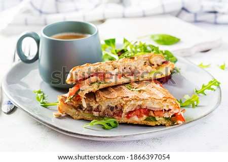 Grilled club sandwich panini with beef, tomato, cheese, lettuce and cup of coffee. Delicious breakfast or snack. Stok fotoğraf ©
