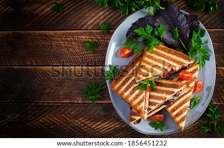 Grilled club sandwich panini with ham, tomato, cheese and leaf mustard. Delicious breakfast or snack. Top view, copy space, overhead Stok fotoğraf ©