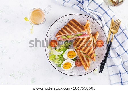 Grilled club sandwich panini with ham, tomato, cheese, avocado and cup of coffee. Delicious breakfast or snack. Top view, flat lay Stok fotoğraf ©