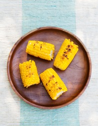 Grilled corn on the cob with salt and butter on a wooden plate Top view Copy space