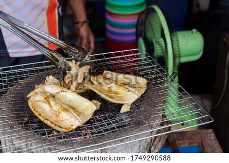 Grilled Cuttlefish on a charcoal stove. Grilled squid is very tasty.Can found at street food,Thailand. BBQ Grill On Hot Charcoal.Grilled fresh squid on a grill with charcoal grill.