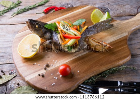 Grilled dorado fish stuffed with different vegetables