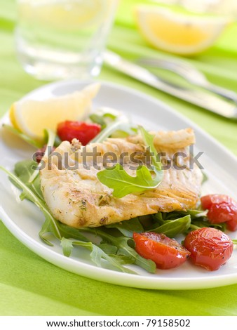 Grilled fish fillet with tomato and lemon. Selective focus