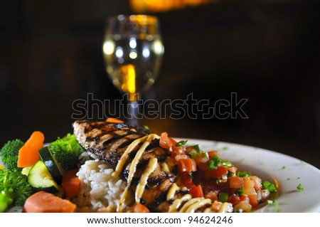 Grilled fish on a white plate with rice and vegetables glass of wine