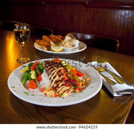 Grilled fish on a white plate with rice and vegetables glass of wine and second dish in the back