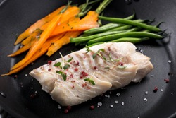 grilled fish with green beans and carrots on frying pan