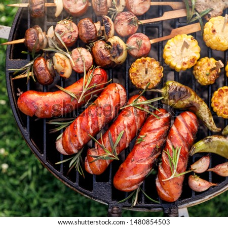 Grilled food, assorted of grilled products, grilled sausages, skewers and vegetables on a bbq grill plate, outdoor, close-up.  #1480854503