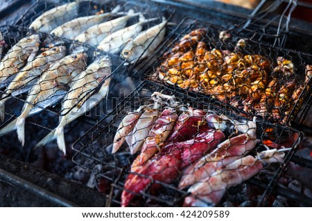 Grilled fresh seafood: prawns, fish, octopus, oysters food background Barbecue / Cooking BBQ seafood on fire / Indonesia