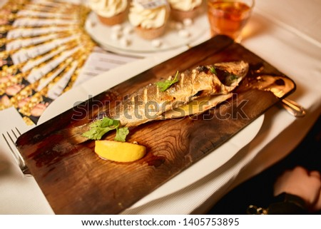 Grilled fresh trout served with lemon on wooden plate #1405753895