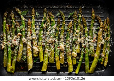 Grilled green asparagus with the addition of parmesan cheese, garlic and aromatic herbs on the grill plate, top view, close-up. Vegetarian food
