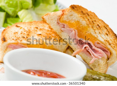 Grilled ham and cheese sandwich with side salad and a pickle - stock ...