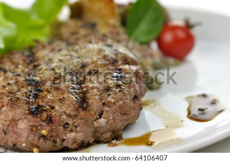 grilled hamburger on a plate with salad