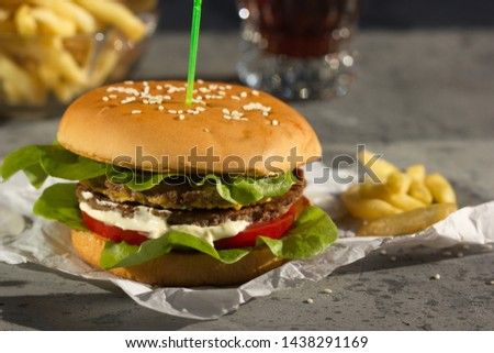 Grilled hamburger with fries and cola on grey background.   Horizontally. #1438291169