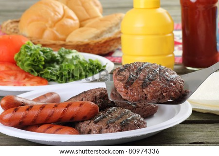 Grilled hamburgers, with one on a spatula, and hot dogs on a picnic table