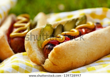 Grilled hot dogs with mustard, ketchup and relish on a picnic table