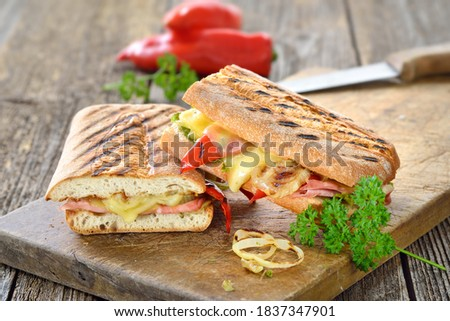 Grilled Italian ciabatta bread with ham, cheese and vegetables served on a wooden cutting board  Stok fotoğraf ©