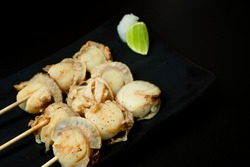 Grilled Japanese hotate scallops served in Japanese restaurant. Grilled hotate scallops is Japanese style of sea food cooking. Japanese grilled hotate scallops and Asian restaurant concept. Copy space