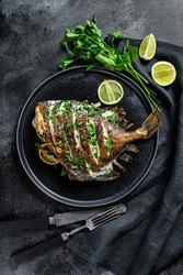 Grilled John Dory fish with lime and parsley in a pan. Black background. Top view