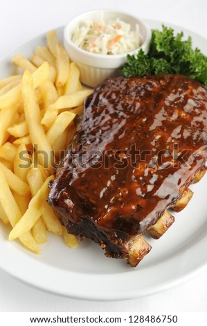 Grilled juicy barbecue pork ribs in a white plate with fries, coleslaw and parsley.