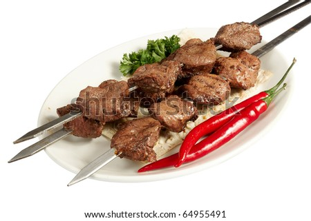 Grilled kebab meat with parsley, paprika and cake on white plate