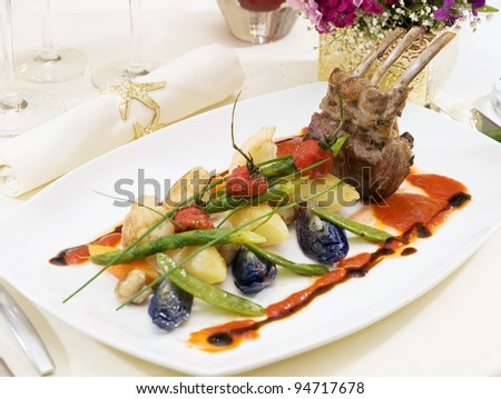 Grilled lamb served on potato with tomatoes and raisins, goat cheese pastry and smoked tomato and butter sauce