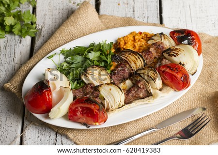 Grilled lamb shish kebab ( sogan kebabi ) on white plate with rustic serving board, spicy tomato sauce, herbs, onion, bugur and grilled hot green pepper over white wooden backdrop, Angle view.