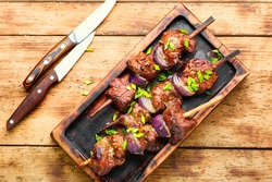 Grilled liver kebab with onion on skewers.Shish kebab on wooden background