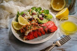 Grilled lobster tail served with fresh Greek salad with sliced lemon and melted butter for dipping