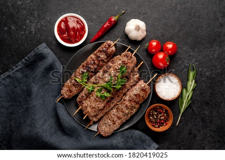 Grilled Lula kebab on skewers with spices in a black plate on a stone background